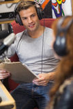 Attractive happy radio host interviewing a guest holding clipboard Royalty Free Stock Image