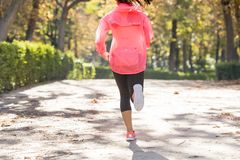 Attractive and happy runner woman in Autumn sportswear running and training on jogging outdoors workout in city park Stock Photo
