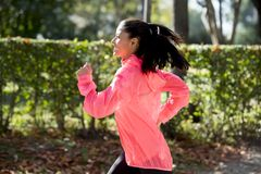 Attractive and happy runner woman in Autumn sportswear running and training on jogging outdoors workout in city park Stock Photos