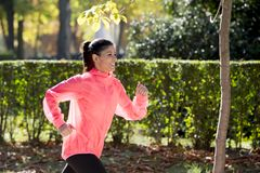 Attractive and happy runner woman in Autumn sportswear running and training on jogging outdoors workout in city park Stock Images