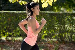 Attractive and happy runner woman in Autumn sportswear running and training on jogging outdoors workout in city park Royalty Free Stock Image