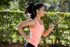 Attractive and happy runner woman in Autumn sportswear running and training on jogging outdoors workout in city park Royalty Free Stock Photography
