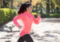 Attractive and happy runner woman in Autumn sportswear running a Stock Image