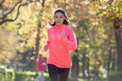 Attractive and happy runner woman in Autumn sportswear running a. Young attractive and happy runner woman in Autumn sportswear running and training on jogging Royalty Free Stock Photos