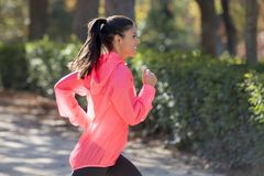 Attractive and happy runner woman in Autumn sportswear running a Royalty Free Stock Images