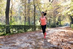 Attractive and happy runner woman in Autumn sportswear running a Stock Photography