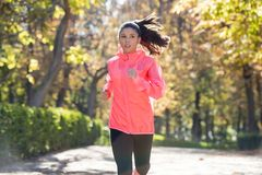 Attractive and happy runner woman in Autumn sportswear running a Stock Photo
