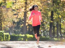 Attractive and happy runner woman in Autumn sportswear running a royalty free stock photos