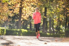 Attractive and happy runner woman in Autumn sportswear running a Royalty Free Stock Photo