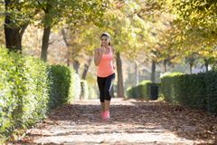 Attractive and happy runner woman in Autumn sportswear running a. Young attractive and happy runner woman in Autumn sportswear running and training on jogging Stock Photo