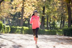 Attractive and happy runner woman in Autumn sportswear running a. Young attractive and happy runner woman in Autumn sportswear running and training on jogging Royalty Free Stock Images