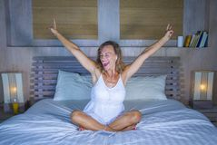 Attractive and happy 30s Caucasian blond woman in bed at home bedroom listening to music internet song with headphones and mobile. Attractive and happy 30s Stock Photography