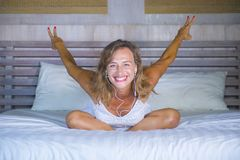 Attractive and happy 30s Caucasian blond woman in bed at home bedroom listening to music internet song with headphones and mobile. Attractive and happy 30s Stock Images