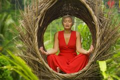 Attractive and happy 40s or 50s middle aged Asian woman in classy and beautiful red dress practicing yoga relaxation and. Outdoors natural portrait of attractive royalty free stock images