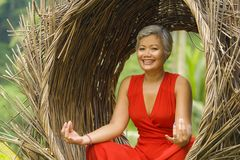 Attractive and happy 40s or 50s middle aged Asian woman in classy and beautiful red dress practicing yoga relaxation and. Outdoors natural portrait of attractive stock image