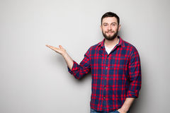 Attractive happy smiling casual young man in shirt holding copyspace on palm and showing okay gesture over gray background Royalty Free Stock Image