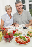 Middle Aged Couple Healthy Eating Salad Table. An attractive happy, smiling middle aged couple healthy eating salad, seafood, cold meats and fruit at a dining Royalty Free Stock Photography