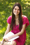 Attractive happy smiling student teen girl reading book in park Stock Images
