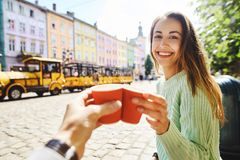 Attractive happy smiling woman sitting in the center of old city with paper cup of coffee Stock Image
