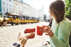 Attractive happy smiling woman sitting in the center of old city with paper cup of coffee Royalty Free Stock Photography
