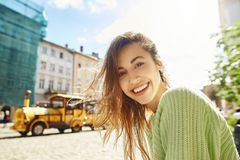 Attractive happy smiling woman sitting in the center of old city Royalty Free Stock Photos