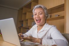 Attractive and happy successful middle aged business Asian woman working at laptop computer desk smiling confident in entrepreneur stock images