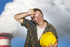 Attractive happy and tired contractor or construction worker man holding safety helmet and dirt stained face at smoking factory royalty free stock photography