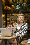Attractive happy  woman is drinking coffee and using laptop in a coffee shop. Stock Image