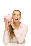 Attractive happy woman holding piggybank. Attractive young woman over white background Stock Photo