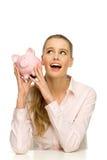 Attractive happy woman holding piggybank Stock Photo