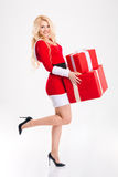 Attractive happy woman in red santa claus costume holding presents royalty free stock photos