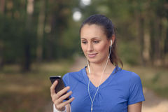 Attractive happy woman standing listening to music Royalty Free Stock Photos