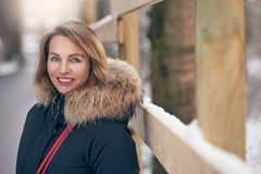 Attractive happy woman standing outdoors in winter. Wearing a fur trimmed jacket alongside a widow sill with fresh white snow in an urban street looking to the stock photo