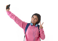 Attractive and happy woman or student girl with backpack and headphones taking selfie photo Royalty Free Stock Photography