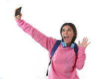 Attractive and happy woman or student girl with backpack and headphones taking selfie photo Royalty Free Stock Photo