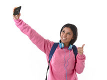 Attractive and happy woman or student girl with backpack and headphones taking selfie photo Stock Photos