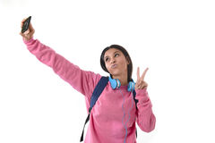 Attractive and happy woman or student girl with backpack and headphones taking selfie photo Stock Photo