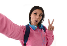 Attractive and happy woman or student girl with backpack and headphones taking selfie photo Royalty Free Stock Images