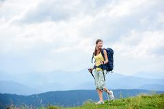 Woman hiker hiking on grassy hill, wearing backpack, using trekking sticks in the mountains. Attractive happy woman tourist hiking mountain trail, walking on stock image