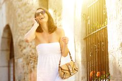 Attractive happy woman walking in town with cell phone Stock Photos