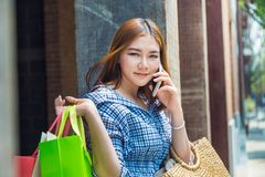 Attractive happy young asian woman carrying her shopping bags ov Royalty Free Stock Photo