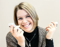 Attractive happy young businesswoman chatting on two smartphones Royalty Free Stock Images