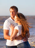 Attractive happy young couple cuddling at the beach. Royalty Free Stock Images