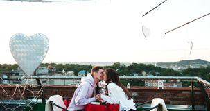 Attractive happy young couple holding hands and softly rubbing noses during the date on the roof decorated with metal stock footage
