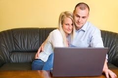 Attractive happy young couple with laptop. Stock Photography