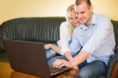 Attractive happy young couple with laptop. Stock Photos