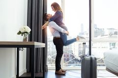 Attractive happy young couple in love having fun and hugging in hotel room royalty free stock images