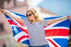 Attractive happy young girl with the flag of the Great Britain. Kingdom brexit united woman english student lifestyle study background england british people stock image