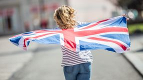 Attractive happy young girl with the flag of the Great Britain. Kingdom brexit united woman english student lifestyle study background england british people royalty free stock photography