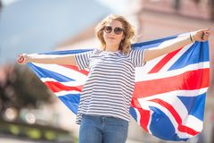 Attractive happy young girl with the flag of the Great Britain. Kingdom brexit united woman english student lifestyle study background england british people stock photography